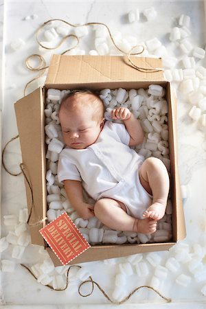 fragile - High Angle View of Newborn Baby Girl in a White Onesie in a Shipping Box Labeled as a Special Delivery with Packing Foam and Twine Stock Photo - Rights-Managed, Code: 700-06532016