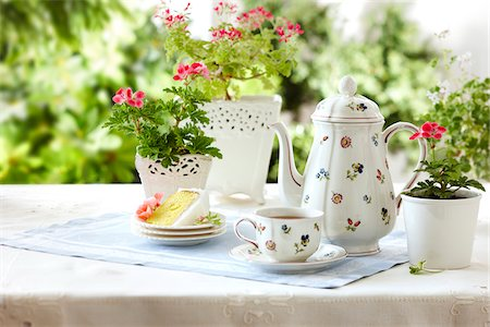 tablesetting with tea, teacup, teapot, cake, and edible geraniums as well as potted flowering geraniums in a garden setting Stock Photo - Rights-Managed, Code: 700-06532026