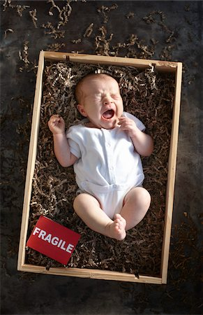 yawning newborn baby girl wearing white undershirt onesie in a shipping box labeled as fragile with packing paper Stock Photo - Rights-Managed, Code: 700-06532020