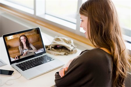 Woman in library using a laptop to have a video chat with her friend Stock Photo - Rights-Managed, Code: 700-06553290