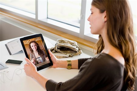 Woman in library using a tablet computer to have a video chat with her friend Stock Photo - Rights-Managed, Code: 700-06553291