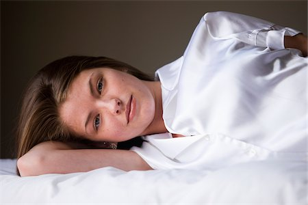 silky - Portrait of woman lying on her bed in her bedroom. Stock Photo - Rights-Managed, Code: 700-06553301