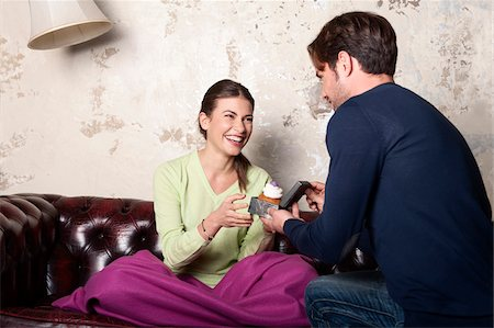Young Man with Cupcake Proposing to Woman at Home Stock Photo - Rights-Managed, Code: 700-06553388