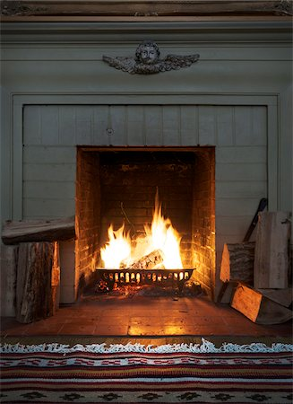 view of fireplace with roaring fire and firewood Stock Photo - Rights-Managed, Code: 700-06570970