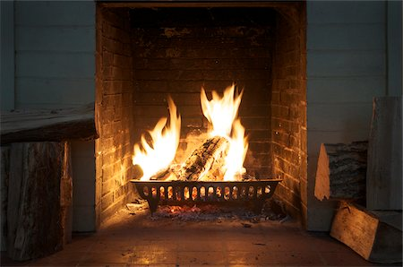 view of fireplace with roaring fire and firewood Stock Photo - Rights-Managed, Code: 700-06570971