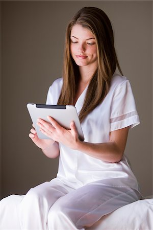 silky - Woman sitting on bed using an ipad. Stock Photo - Rights-Managed, Code: 700-06674973