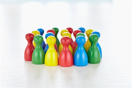 Huddle of multi-colored playing pieces standing together in a group like people Stock Photo - Rights-Managed, Code: 700-06679362