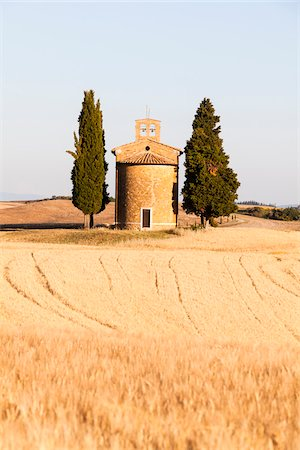 Cappella di Vitaleta framed by cypress trees (cupressus sempervirens), barley field in summer, Val d'Orcia, Tuscany, Italy Stock Photo - Rights-Managed, Code: 700-06701736