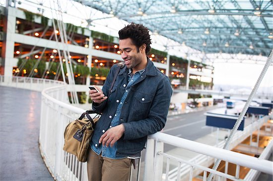Smiling Man Texting on Cell Phone at the Airport Stock Photo - Premium Rights-Managed, Artist: Boone Rodriguez, Image code: 700-06701846