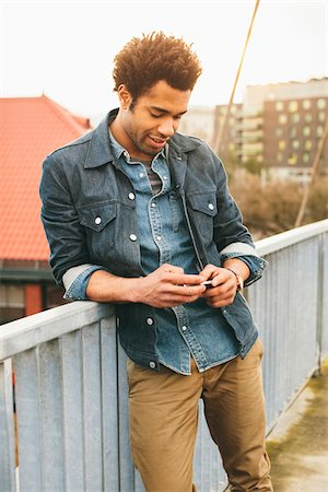 Young man texting on an iPhone in an urban setting. Stock Photo - Rights-Managed, Code: 700-06701842