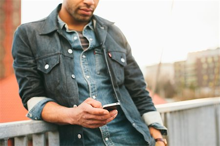 Close-up of young man texting on an iPhone in an urban setting. Stock Photo - Rights-Managed, Code: 700-06701843