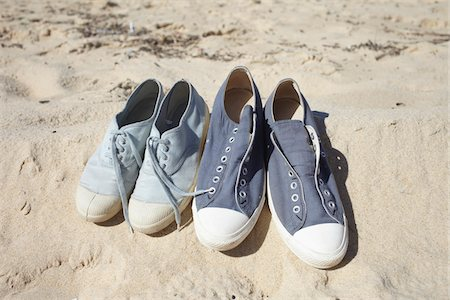 Two pairs of blue sneaker shoes on sand at the beach Stock Photo - Rights-Managed, Code: 700-06714055