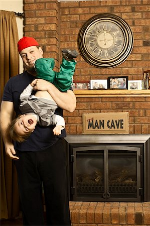 Father and Son Playing by Fireplace in Man Cave Stock Photo - Rights-Managed, Code: 700-06758135
