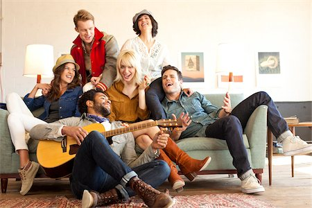 friend (female) - Group of well styled young adults playing guitar and singing on a couch. Stock Photo - Rights-Managed, Code: 700-06752634
