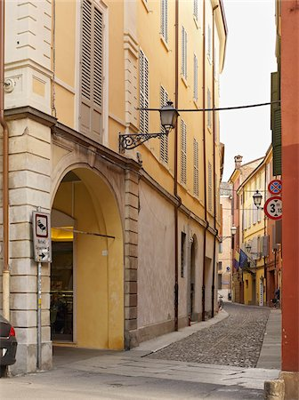 narrow cobblestone street lined with archways and yellow buildings, Modena, Italy Stock Photo - Rights-Managed, Code: 700-06773316