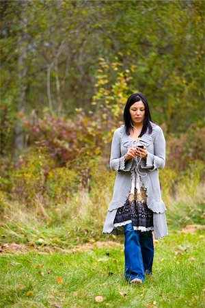 Woman with smart phone wearing earbuds and walking outdoors Stock Photo - Rights-Managed, Code: 700-06773480