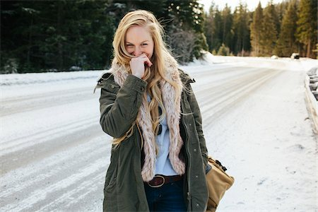 Blonde Woman Walking with Duffel Bag by Snow Covered Road Stock Photo - Rights-Managed, Code: 700-06786683