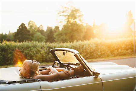 Teenage girl laying back in a 1966 Triumph in Portland Oregon. Stock Photo - Rights-Managed, Code: 700-06786692