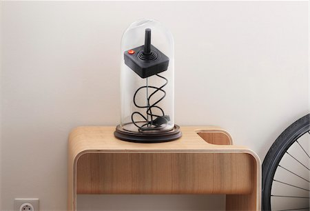 iconic joystick under glass cover on wooden table Stock Photo - Rights-Managed, Code: 700-06786719