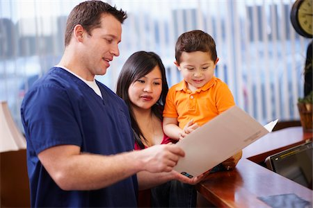 Dentist with file folder talking with mother and child. Stock Photo - Rights-Managed, Code: 700-06786943