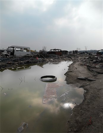 Tire floating in puddle in burnt out wasteland, Saint Denis, France Stock Photo - Rights-Managed, Code: 700-06808740