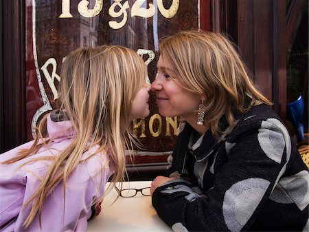 Mother and daughter nose-to-nose on terrace of french cafe, Paris, France Stock Photo - Rights-Managed, Code: 700-06808775