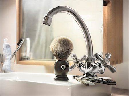 Straight razor and shaving brush on edge of bathroom sink with blood type indicated on shaving brush Stock Photo - Rights-Managed, Code: 700-06808770