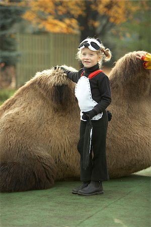 Girl in panda halloween costume standing next to camel Stock Photo - Rights-Managed, Code: 700-06808831