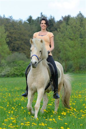 Young woman riding a icelandic horse on a meadow in spring, Germany Stock Photo - Rights-Managed, Code: 700-06808856