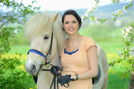 dark hair - Portrait of a young woman with a icelandic horse standing under a flowering cherry tree in spring, Germany Stock Photo - Rights-Managed, Code: 700-06808857
