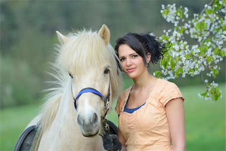 dark hair - Portrait of a young woman with a icelandic horse standing under a flowering cherry tree in spring, Germany Stock Photo - Rights-Managed, Code: 700-06808859