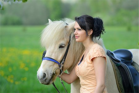 dark hair - Young woman with a icelandic horse standing on a meadow in spring, Germany Stock Photo - Rights-Managed, Code: 700-06808860