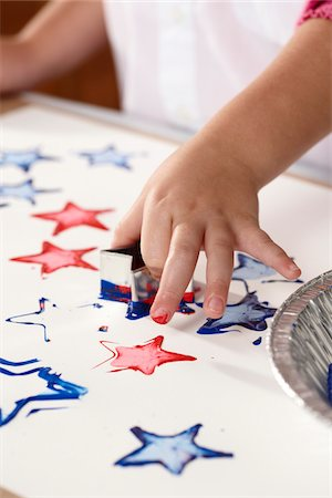 stamping (all meanings) - Close-up of child's hand stamping star-shapes in paint on a sheet of paper Stock Photo - Rights-Managed, Code: 700-06895096