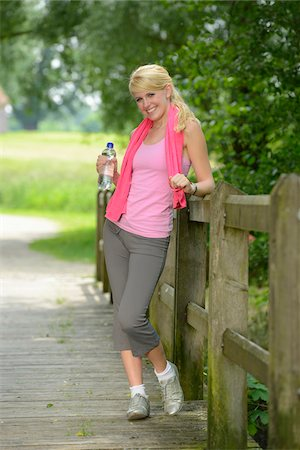 Portrait of blond woman wearing exercise clothing and holding bottle of water outdoors, Germany Stock Photo - Rights-Managed, Code: 700-06899963