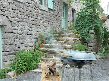 Smoking barbecue grill outside home, Labeaume, France Stock Photo - Rights-Managed, Code: 700-06892573