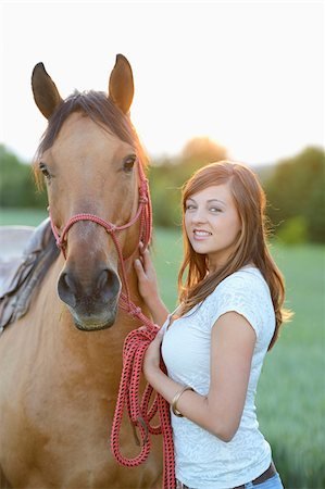 dark hair - Young attractive woman standing beside a horse on a meadow by sunset, Germany Stock Photo - Rights-Managed, Code: 700-06936035