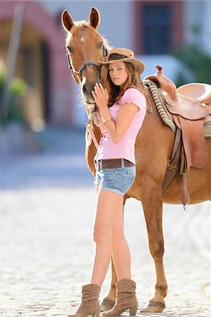 Young attractive woman standing beside a horse at a castle forecourt, Germany Stock Photo - Rights-Managed, Code: 700-06936030
