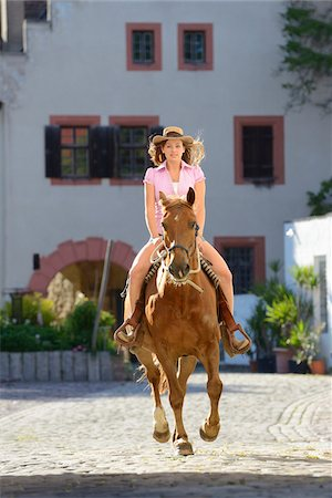 Young attractive woman riding a horse at a castle forecourt, Germany Stock Photo - Rights-Managed, Code: 700-06936032