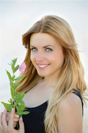 Portrait of a young woman with a flower outdoors in summer, Germany Stock Photo - Rights-Managed, Code: 700-06936129
