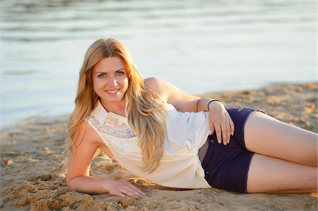 Young woman lying on a sandy beach at the shore of a lake, Germany Stock Photo - Rights-Managed, Code: 700-06939626