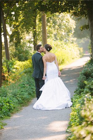 Backview of Bride and Groom kissing and holding hands, walking down pathway outdoors, on Wedding Day Stock Photo - Rights-Managed, Code: 700-06939704