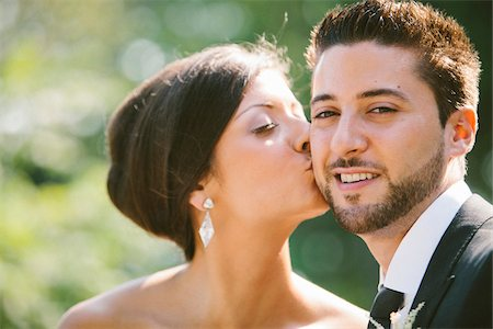 Close-up, outdoor portrait of Bride kissing Groom on cheek Stock Photo - Rights-Managed, Code: 700-06939703