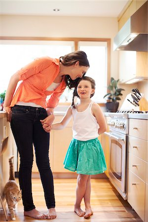 daughter kissing mother - Mother and daughter in a kitchen. Stock Photo - Rights-Managed, Code: 700-06943756