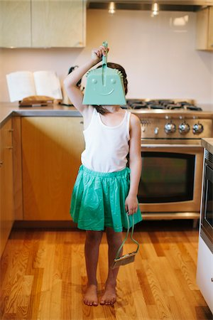 Young girl holding dustpan in front of face, standing in kitchen. Stock Photo - Rights-Managed, Code: 700-06943757