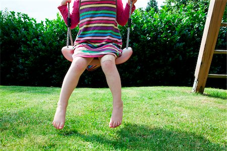 Girl sitting on a swing in backyard Stock Photo - Rights-Managed, Code: 700-06961790