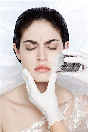 Woman with eyes closed wrapped in plastic, with hands in latex glove scrubbing face with scourng pad, studio shot Stock Photo - Rights-Managed, Code: 700-06961985