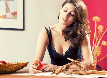 Portrait of woman in lingerie sitting at table holding apple, Germany Stock Photo - Rights-Managed, Code: 700-06961987
