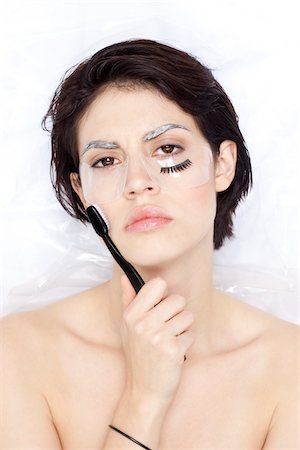 Close-up portrait of woman wrapped in plastic and holding toothbrush, dying eyebrows with false eyelash on face, studio shot Stock Photo - Rights-Managed, Code: 700-06961983