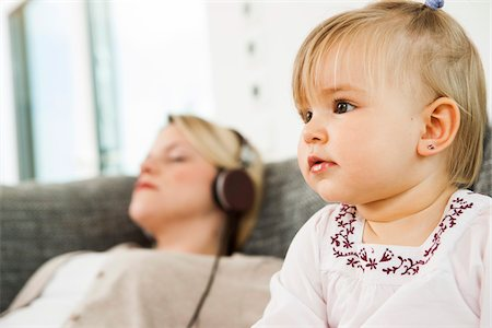 Baby Girl with Mother Listening to Music through Headphones in the background, Mannheim, Baden-Wurttemberg, Germany Stock Photo - Rights-Managed, Code: 700-06962012