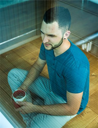 drink (non-alcohol) - Young Man Sitting on Floor with Coffee Cup, Mannheim, Baden-Wurttemberg, Germany Stock Photo - Rights-Managed, Code: 700-06962060